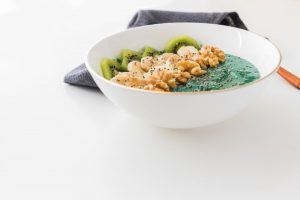spirulina smoothie bowl with banana walnuts kiwi and chia seeds on white background1