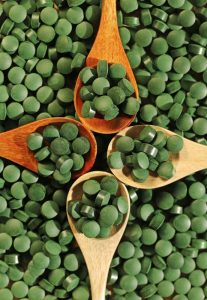 spirulina tablets in wooden spoons top view